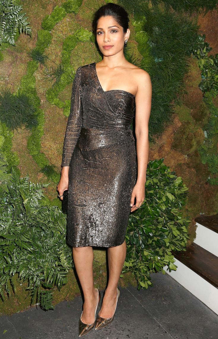 FREIDA PINTO wears a metallic one-sleeve cocktail dress, matching pumps, an Edie Parker clutch and rings and earrings by John Hardy at the John Hardy Artisan in Residence Launch in N.Y.C.