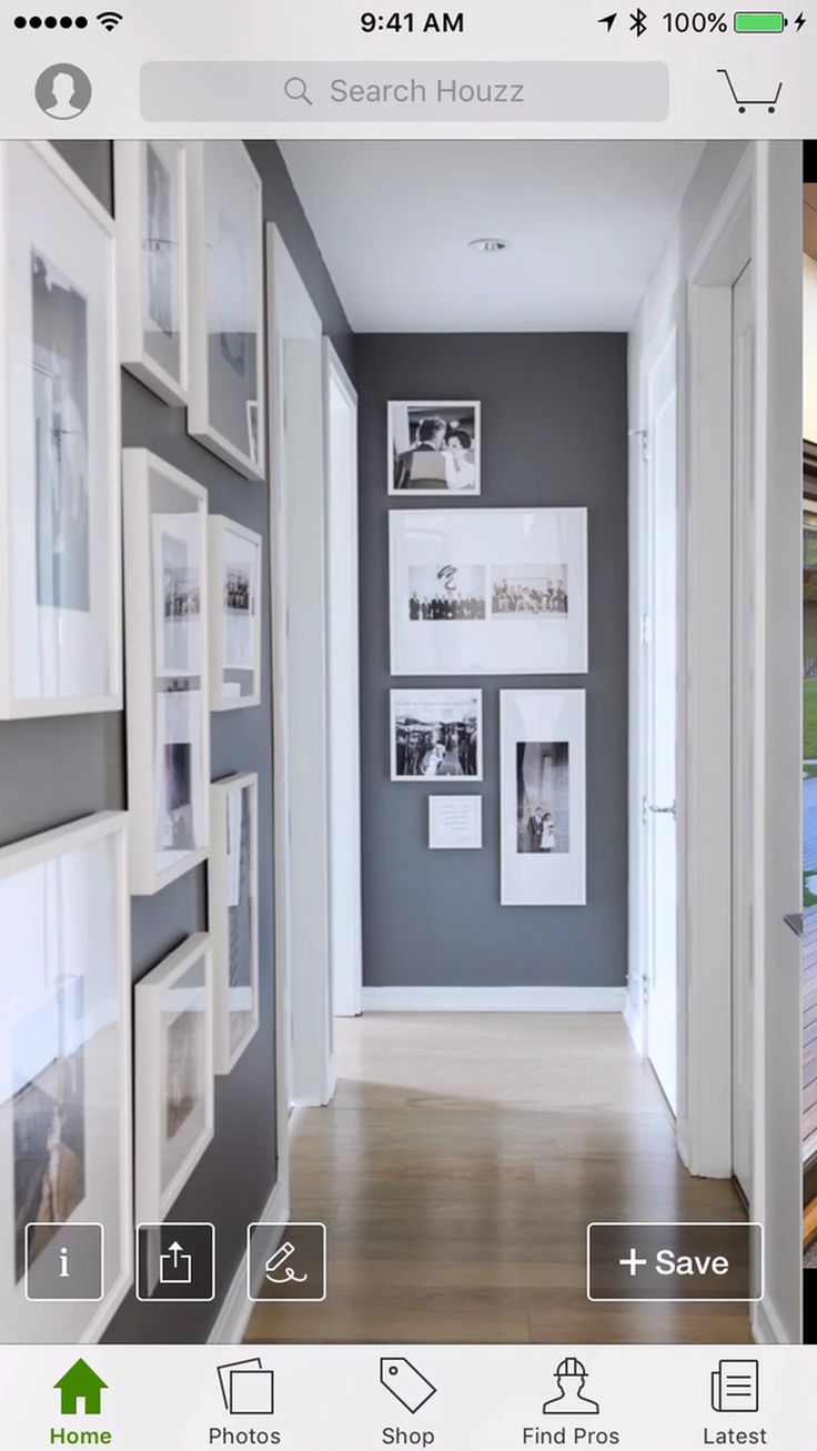 Beautiful hallway boasts dark gray accent walls painted Benjamin Moore  Kendall Charcoal studded with photo gallery wall in white gallery frames  across from ...