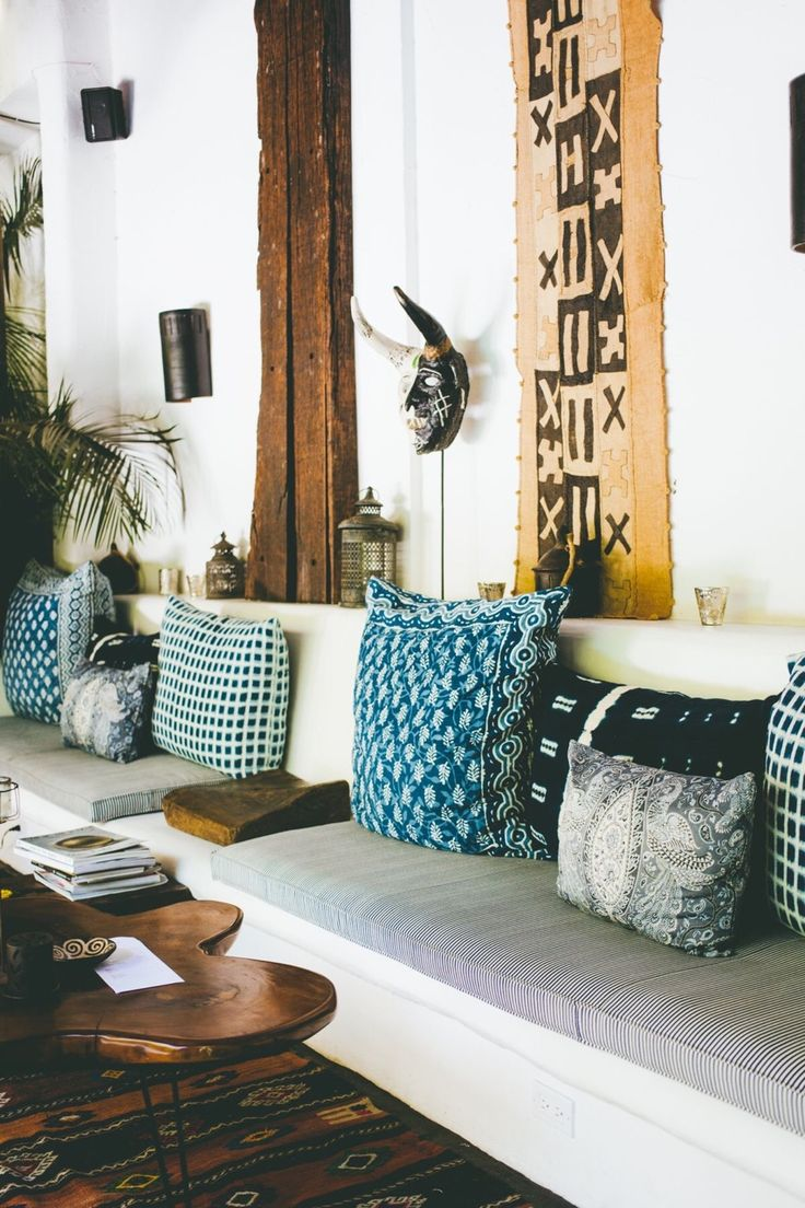 A grouping of tribal print pillows and cushions on a banquette with indigo and shades of blue