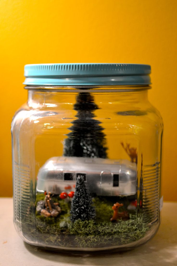 Miniature Spring Airstream Scene with deer, pine trees, mushrooms, and campfire, and LED lights in glass jar with painted blue lid.
