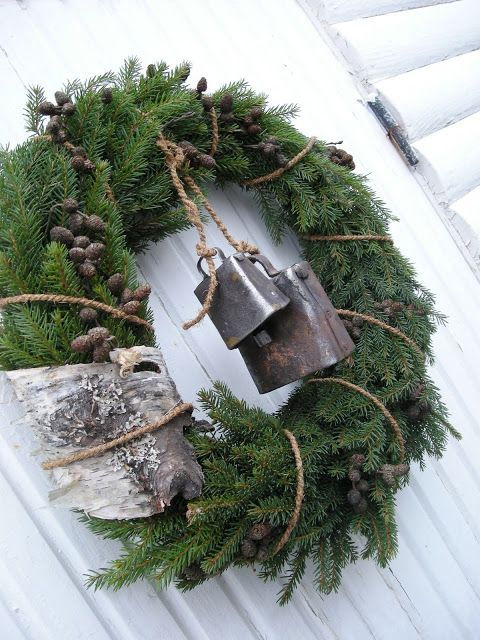 Christmas greenery wreath with cow bells angling from rope...I love the simplicity of this wreath..cute or a farm, and the bells would ring anytime someone entered..