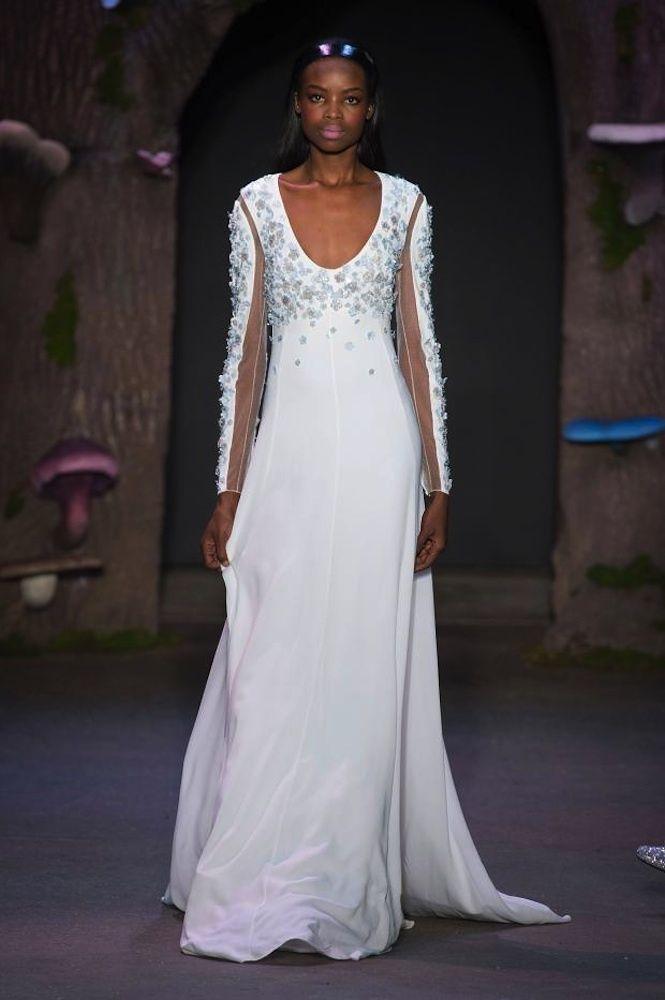Vestidos de pasarela para novias no convencionales. De la firma Honor. Vestido largo en color blanco con pequeña cola. Lleva mangas largas con transparencias y flores 3D brillantes en color azul celeste en escote y mangas.