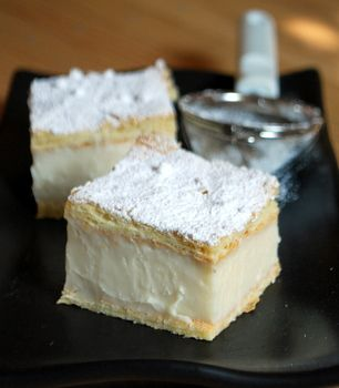 Vanilla Slice...Ingredients: 2 sheets puff pastry (1 package Pepperidge Farm), defrosted; 2 cups milk; 1 vanilla bean; 2 cups half n' half; 1 cup sugar; 3/4 cup cornstarch; 1/2 cup custard powder or instant vanilla pudding. 3 large egg yolks 1 1/2 tsp vanilla extract 4 tbsp butter, room temperature confectioners' sugar