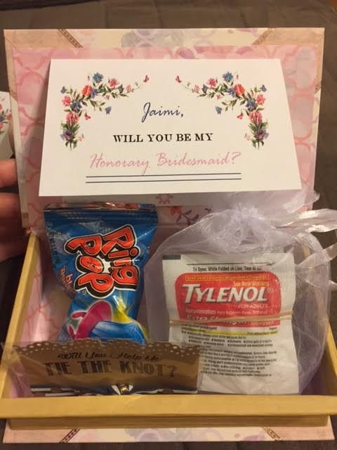 "My Honorary Bridesmaid Box. I got the super cute box that looks like a book from Michaels. I got the ""Will you help me tie the knot"" Hair tie from Etsy. Ringpop from Party city, and I put Tylenol, Advil, and Aleve in the pouch. I also made and printed the signs myself."