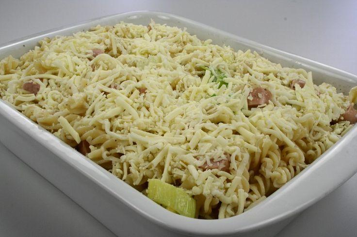 Pasta koges som anvist på posen og hældes i et ovnfast fad. <BR>  Rens porrerne, skær dem i skiver og giv dem et let opkog. <BR> <BR> Kom porrerne i fadet sammen med pasta og majs. Skær pølserne i