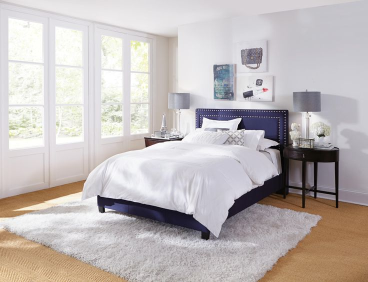 The sophisticated Davis Navy Upholstered Bed offers a clean line silhouette headboard, with double large shiny nail head detailing. Stocked in queen and king size.