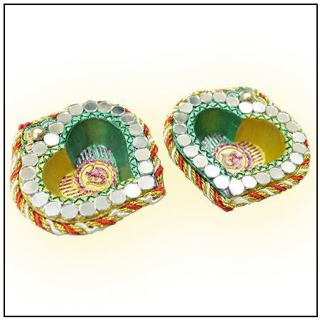 Vedicvaani.com| Buy Designer Clay Diya in Heart Shape Online, Om Designer Diya, Designer diyas in heart shape with auspicious OM symbol in the center. A Diya is an oil lamp,made from clay,with a cotton wick dipped in ghee or vegetable oils.Clay diyas are often used temporarily as lighting for special occasion.Diyas are native to India.