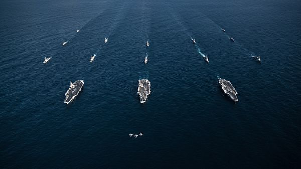 WESTERN PACIFIC (Nov. 12, 2017) Three F/A-18E Super Hornets, assigned to the Eagles of Strike Fighter Attack Squadron (VFA) 115, fly in formation over the aircraft carriers USS Ronald Reagan (CVN 76), USS Theodore Roosevelt (CVN 71), USS Nimitz (CVN 68) and their strike groups along with ships from the Republic of Korea Navy as they transit the Western Pacific. The strike groups are underway and conducting operations in international waters as part of a three-carrier strike force exercise.