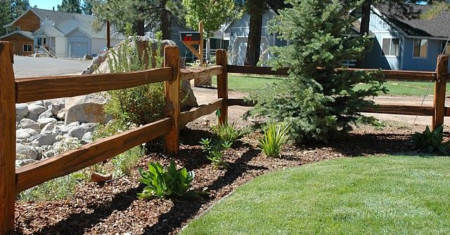 This cedar split rail fence has a casual, country look perfect for a ranch-style home. The light-colored stonework on the other side of the fence makes a beautiful contrast. By Peak Landscape Inc in Truckee, CA.