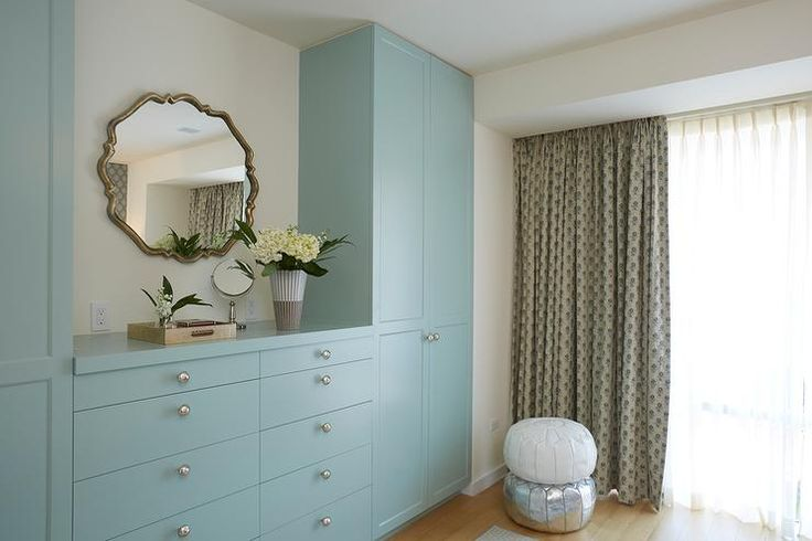 Chic bedroom features a 10 drawer blue built-in dresser adorned with nickel knobs placed under a mirror flanked by floor to ceiling blue wardrobe cabinets.