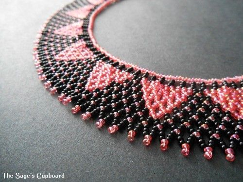 The collar is made up of tiny seed bead nets, with a pattern of pink polka dots on black, and a row of solid pink inverted triangles along the inner edge. The soft pink beads have a shimmery finish an