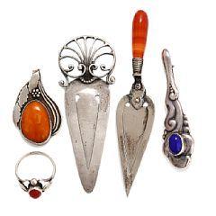 Sølvsmykkesæt bestående af vedhæng, ring, broche og to clips prydet med henholdsvis agat, rav og blå sten.
