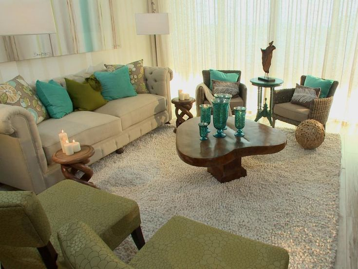 Designer David Bromstad transformed this once empty and lifeless space into a beachy getaway. A neutral palette with pops of sea-inspired color is a breath of fresh air for the living room. The sun-drenched look of the laminate flooring enhances the room's beachy appeal.