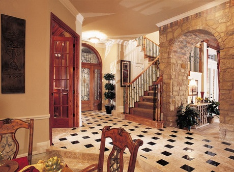 A Checkerboard Marble Floor And Arched Stone Wall. An Entry Door With  Wrought Iron Accents