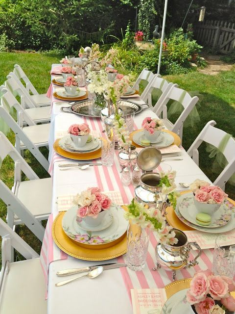 a lovely garden party with roses in each teacup from the enchanted home