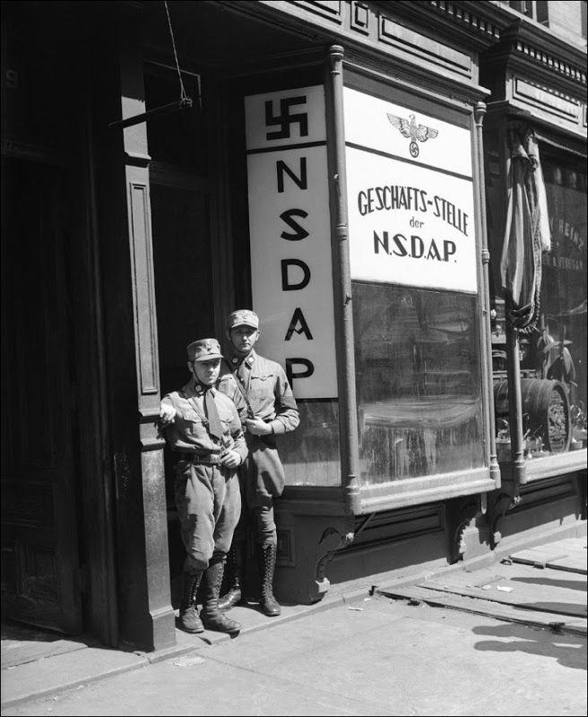 """Nazistas Americanos  Dois nazistas americanos uniformizados na entrada da então recém-inaugurada sede do Partido Nazista em Nova Iorque. """"NSDAP"""" significa Nationalsozialistische Deutsche Arbeiterpartei (Partido Nacional Socialista dos Trabalhadores Alemães, normalmente abreviado para apenas """"Partido Nazista""""). Nova Iorque, 1 de abril de 1932."""
