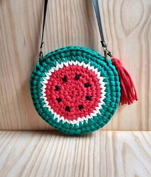650456c3398 Bolsa redonda no tema melancia, confeccionada em crochê com fio de malha,  nas cores vermelho, cru e verde. Medida aproximada: 24 cm de diâmetro e 3  cm de ...