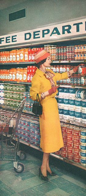 A stylishly attired woman shops for coffee at a Kroger supermarket, 1957.