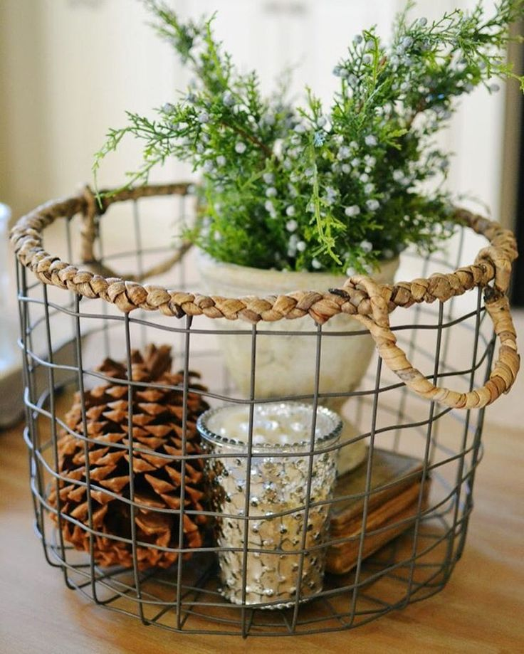 Simple winter decorating...a wire basket filled with a big pinecone, Mercury glass candle for some sparkle and little sprigs of greenery. Doesn't get any easier than that! #winterdecorating #winter