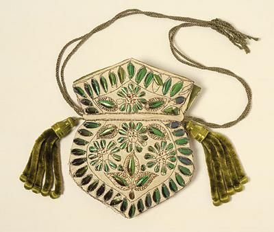 """This bag uses the vivid-green iridescent casings from the wings of an Indian beetle. Known as """"beetle wings"""" these were popular trimming for women's dresses and accessories from the 1830s because of their resemblance to emeralds when seen at a distance or in subdued evening light. Lengths of muslin with applied beetle wings were imported from India to be made up into gowns or shawls, and sometime simple loose ready-made dresses were sent."""