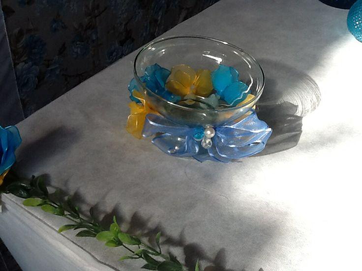 Centro de mesas com flores de meia de seda, dentro do vazinho vai agua e uma vela flutuante, fica muito lindo.