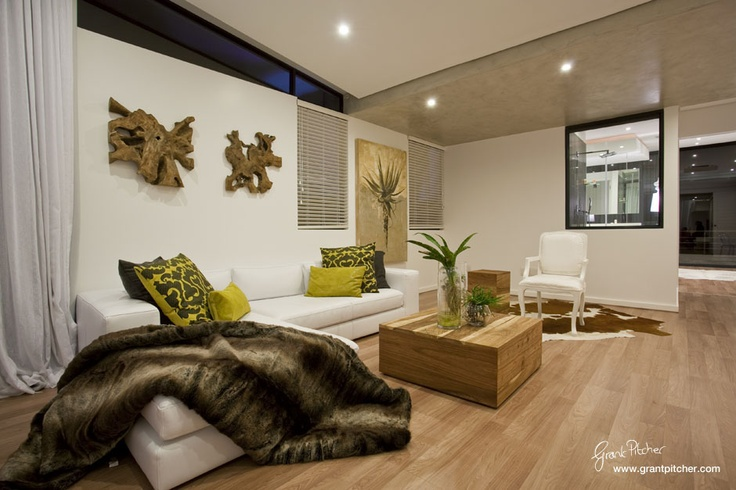 White couch, wooden coffee table, wood wall art, wooden floors