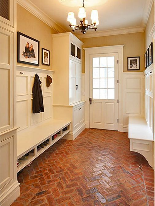 Entryway with built-in storage and brick floor.