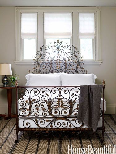 In the guest bedroom, she chose a Moroccan Tuareg mat from F. J. Hakimian as a masculine counterpart to the swirling 19th-century French gilt-and-wrought-iron bed.