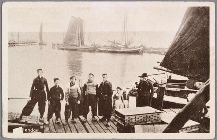 Groep vissers poseert voor de Volendamse haven: zes mannen in werkkleding en drie kleine meisjes in dracht bij de haven. De oude man draagt de ruige muts. Een viskaar op de voorgrond. Botters op de achtergrond, waaronder de BU 173. 1910-1930 #NoordHolland #Volendam