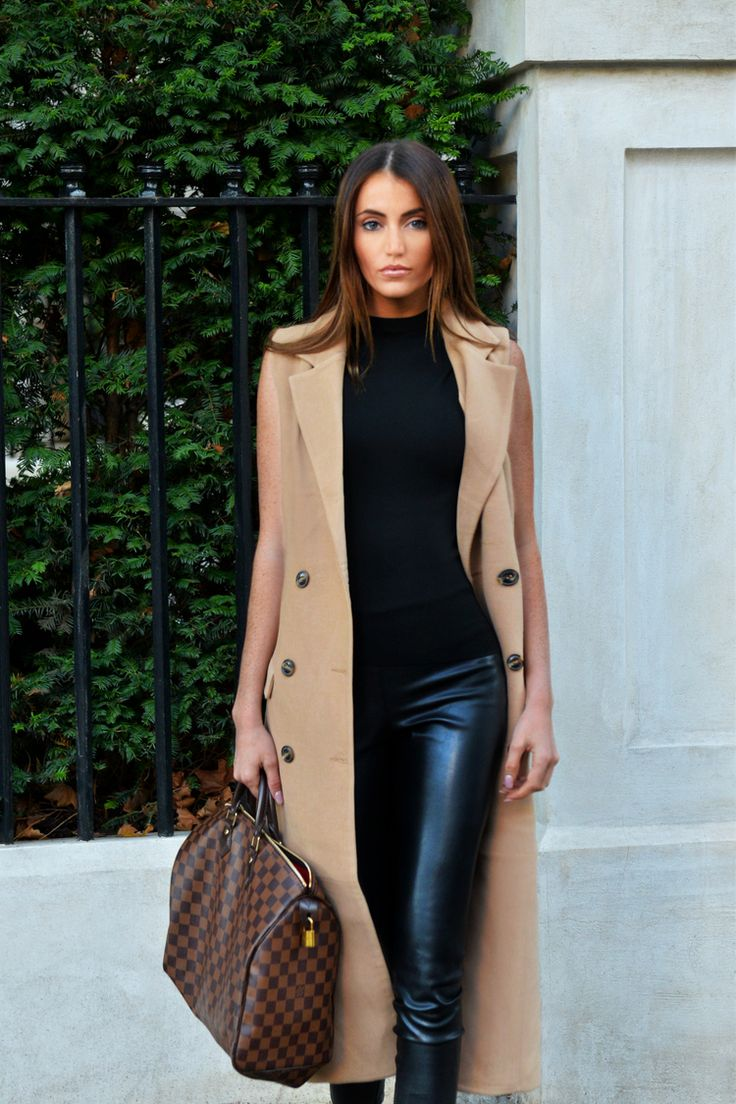 Camel double breasted sleeveless long coat, high waist black leather pants, black patent and suede heeled sneakers by Jimmy Choo