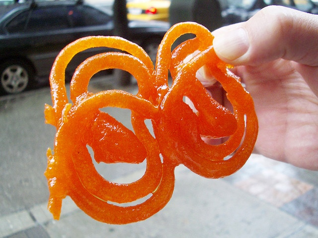 Jalebi (India). 'Jalebis are typically orange-coloured coils of deep-fried  batter, prepared from maida (all-purpose  flour), which are dunked in an intensely sweet sugar syrup. Saffron and rosewater lend a delightfully delicate undertone to this otherwise robust Indian fritter which is a popular year-round sweet snack. Sizzled in ghee (clarified butter) or vegetable oil, jalebis are customarily eaten piping hot from the kadai.