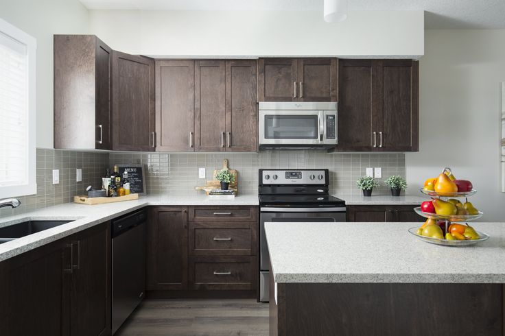 The L-shaped kitchen has a large central island, stainless steel appliances, dark cabinets and light counters creating an eye-catching contrast #kitchen  1 save