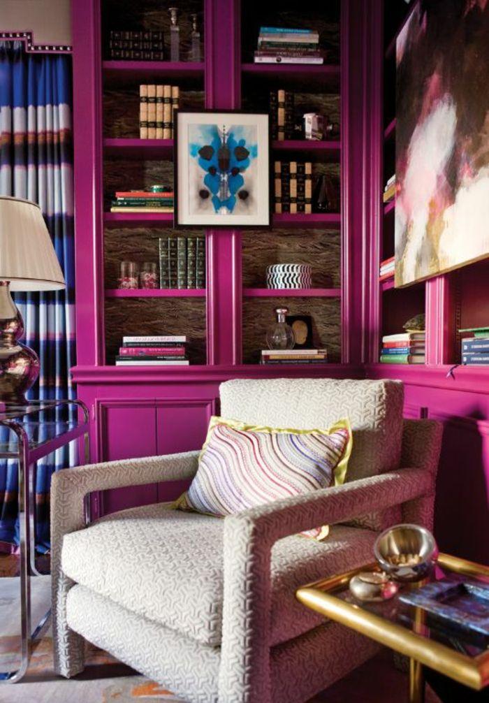 meuble bibliothèque couleur aubergine, tableau abstrait, grand fauteuil cosy, table verre et métal doré