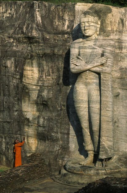 Buddhist monk at the foot of a tall stone Buddha sculpture on a hill. Sri Lanka.