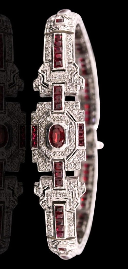 Art Deco 14KT White Gold 4.45ctw Ruby and Diamond Bracelet. Seven and one-eighth inch bracelet features a ruby and diamond plaque supported by a semi-flexible geometric inspired ruby and diamond ribbon, terminating in a concealed clasp with safety bar. The bracelet is reminiscent of the jewelry designs from the Art Deco Period.