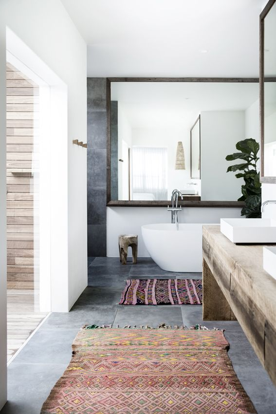 Sleek bathroom with a rustic wood vanity and colorful rugs
