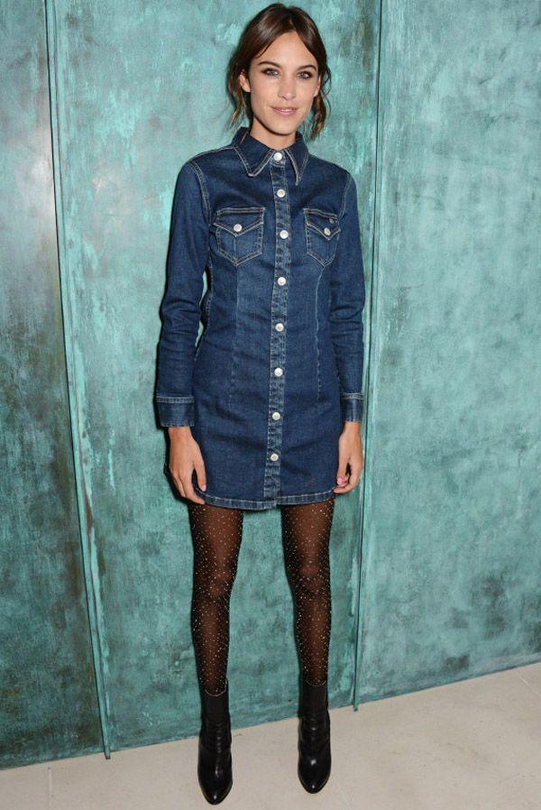 Alexa Chung com vestido jeans meia calça brilhante e bota.