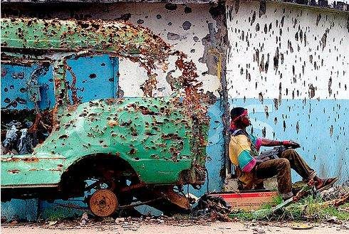 A rebel in Monrovia, Liberia, keeping watch in front of a house and car full of bullet holes