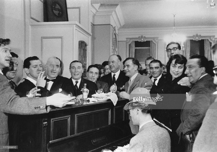 Career criminals and journalists at a party at Gennaro's restaurant in Soho, London, given by British gangster Billy Hill to launch his autobiography 'Boss of Britain's Underworld', December 1955. Left to right: Soho Ted, Bugsy, Groin Frankie, Billy Hill, Ruby Sparkes, Frankie Fraser, College Harry, Frany The Spaniel, Cherry Bill, Johnny Ricco, a female journalist, Russian Ted and a publisher. pub. 3rd December 1953