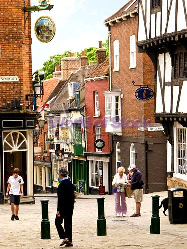 Stock Image of Tourists In The Bailgate Area Of Lincoln England UK At The Top Of Steep Hill Outside The Tourist Information Centre - World of Stock