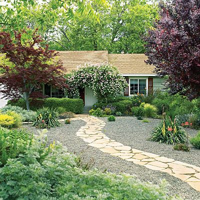 Easy-care front yard    Flagstone paths curve through a low-water front yard. A low berm of soil on either side of the walk adds interest, and weed cloth topped with permeable pea gravel allows excess water to soak into the earth rather than run off into the street.
