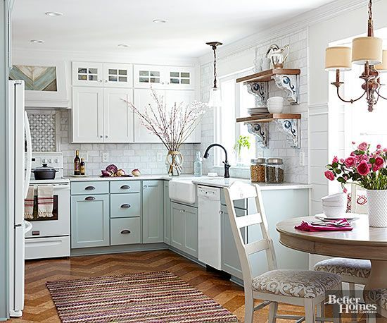 An all-white cottage kitchen is classic, but pretty painted base cabinets in pastel blue make a room shine bright. Cork floor tile installed in a chevron display and a DIY range hood add modern interest to this room's otherwise traditional cottage design elements.