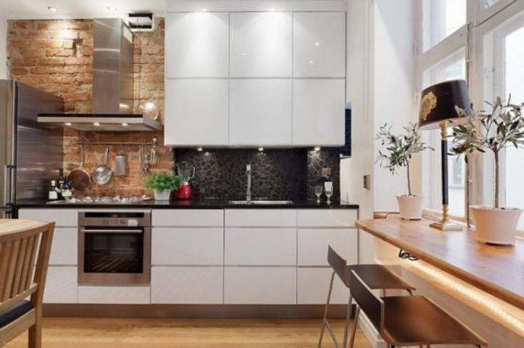 White laminated wooden top cabinet white laminated wooden kitchen island light brown varnished wooden floor natural finish exposed brick wall black ceramic back splash