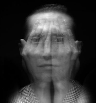 Light used on front of face to make it pop out from the background.  A slow shutter speed has been used in order to get the movement of the hands.