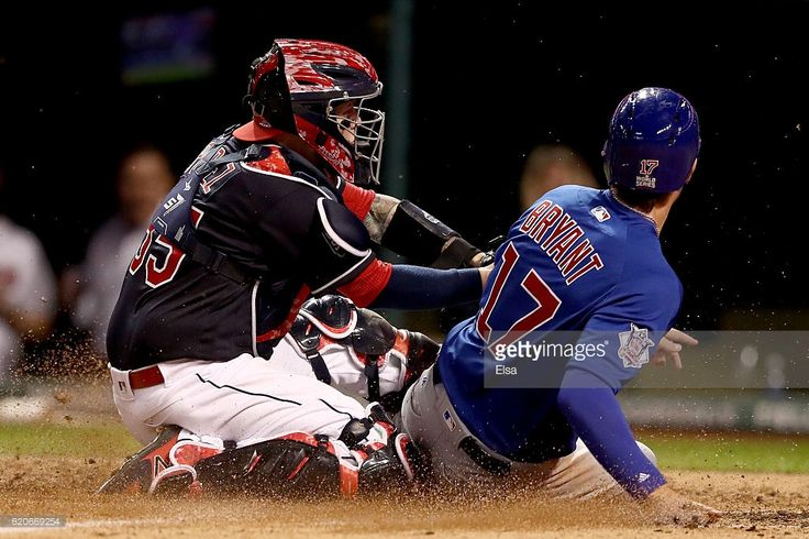 Kris Bryant #17 of the Chicago Cubs scores a run on a sacrifice fly ball hit by Addison Russell #27 (not pictured) as Roberto Perez #55 of the Cleveland Indians is unable to make the tag during the fourth inning in Game Seven of the 2016 World Series at Progressive Field on November 2, 2016 in Cleveland, Ohio.
