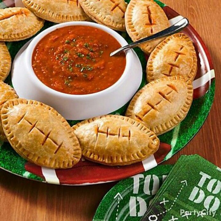 "Football calzones!! To make these football pizza pockets, cut out football shapes from homemade or packaged pastry dough and fill with your favorite ingredients, like mozzarella, pepperoni and pizza sauce. Slice some ""laces"" into the top before baking and serve with a side of marinara for dipping."