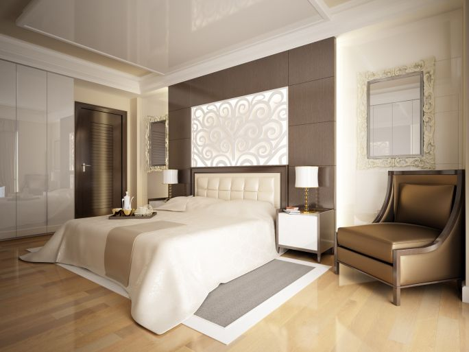 Large light brown and white master bedroom design with large leather chair