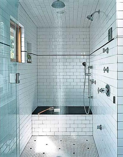 Don't need this many showers but love the subway tiles with dark grout, and wet room idea.