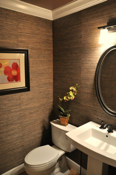 Grasscloth creates instant interest and texture in small powder room. Ceiling is painted copper metallic.