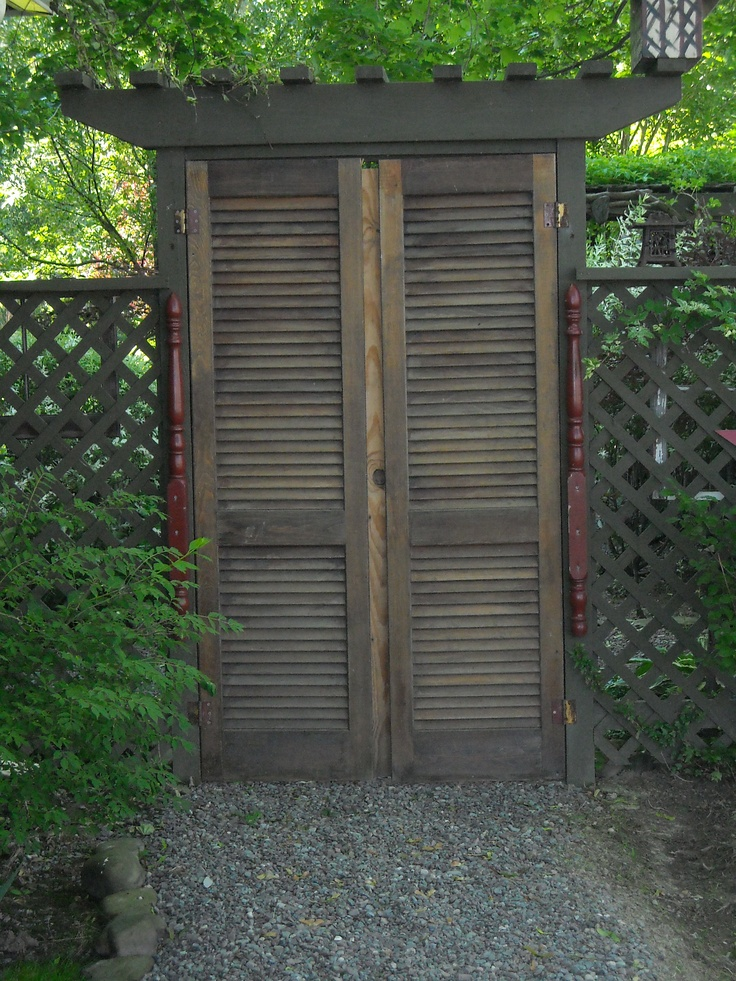 a pair of old recycled shutter doors hang as a garden gate to the back yard!